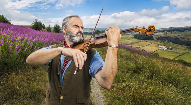 Violin craftsman Steve Burnett poses on the moors above Haworth with his handcrafted Emily Bronte violin (Danny Lawson/PA)