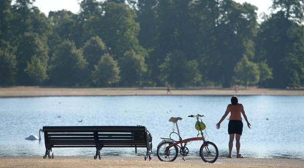 A man enjoys the warm weather by the pond in Kensington Gardens, London (Dominic Lipinski/PA)