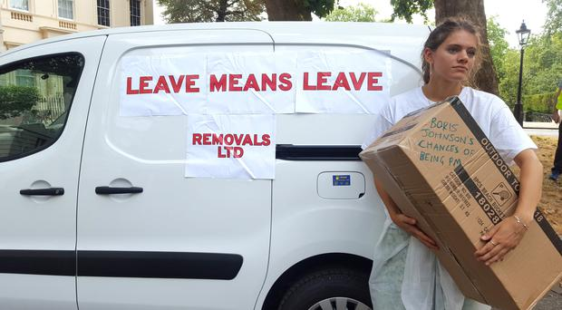 Anti-Brexit campaigner Lara Spirit stands by a van with a removals slogan outside the Foreign Secretary's official residence (Catherine Wylie/PA)