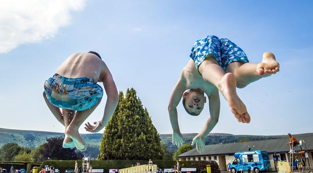 George Cartwright (left) and Alex Hodgkins enjoy the sun at Ilkley Lido in Yorkshire (Danny Lawson/PA)