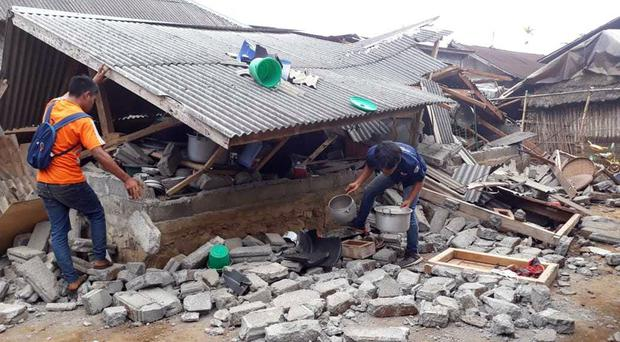 Villagers clear debris caused by the earthquake (AP)