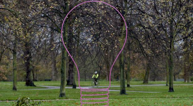 A cyclist passes a light bulb sculpture in London (PA)