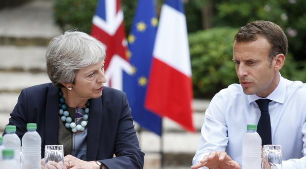 Theresa May cut short her holiday to hold Brexit talks with Emmanuel Macron (Sebastien Nogier/AP)