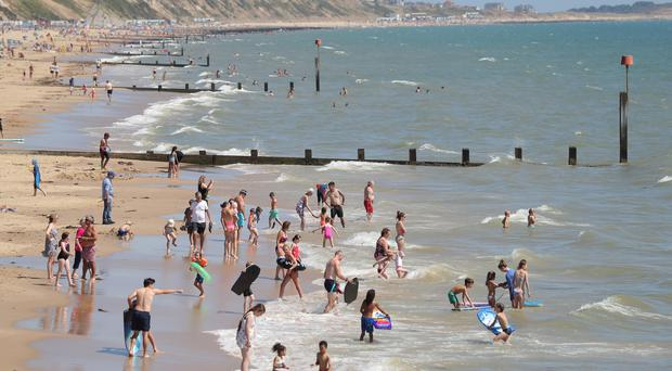 People enjoy the warm weather on Boscombe beach in Dorset (Andrew Matthews/PA)