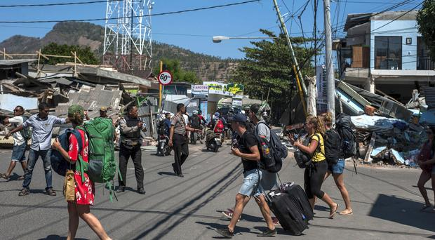 Tourists walk through the streets as they leave an area heavily damaged by the earthquake in Tanjung, Lombok Island (Fauzy Chaniago/AP)