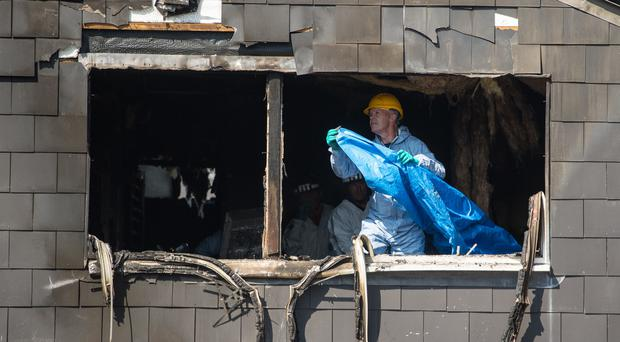 Police and fire investigations officers at the scene of the blaze in Deptford (Dominic Lipinski/PA)