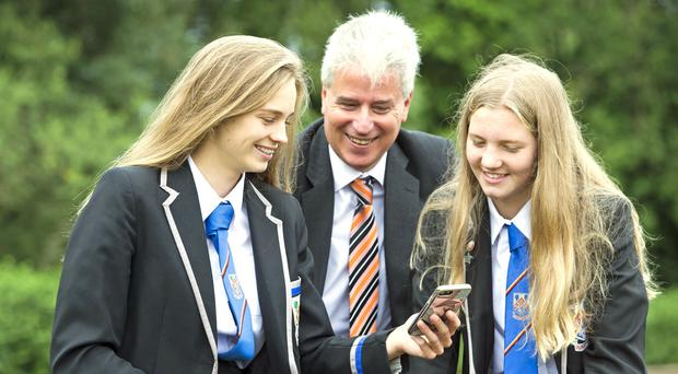 Eastwood High School's head teacher Stuart Maxwell, with pupils Clare Wallace (right) and Erin Wallace, who achieved multiple A's in their exams (Jeff Holmes/PA)