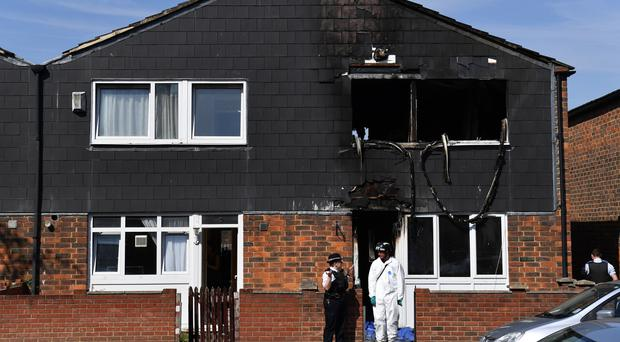 Police and forensics officers at the scene of a house fire in Deptford, south-east London (Dominic Lipinski/PA)