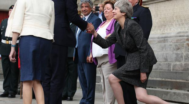 Theresa May gets tripped up by protocol as she makes an awkward curtsy to Prince William at a ceremony to mark 100 years since the Battle of Amiens (PA)
