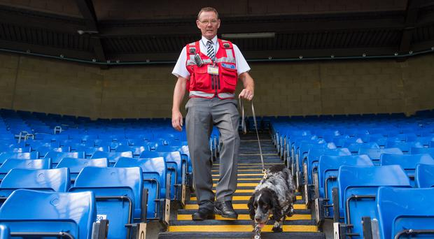 Sniffer dog Charlie and handler Frank Thornborrow check the stands at Chelsea's Stamford Bridge (Dominic Lipinski/PA)