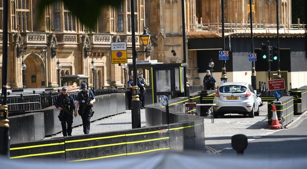 Armed police officers by the car that crashed into security barriers outside the Houses of Parliament (PA/Stefan Rousseau)