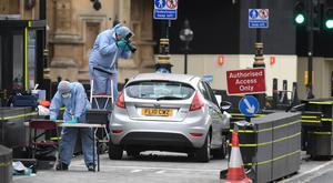 Forensic officers by the car that crashed into security barriers outside the Houses of Parliament, Westminster, London (Victoria Jones/PA)