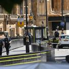 Armed police by the car that crashed into security barriers (Stefan Rousseau/PA)