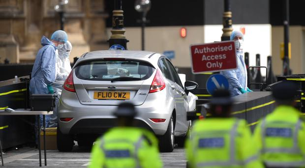 Forensic officers by the car that crashed into security barriers outside the Houses of Parliament (Victoria Jones/PA)