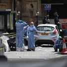 Forensic officers by the car that crashed into security barriers outside the Houses of Parliament (/PA)