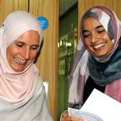 Student Zahra Farooque, 18 (right), holding her results, with her mother Anne Farooque, 42 (Putney High School/PA)