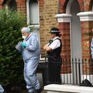 Forensics and a police officer outside a property on Grayshott Road in Battersea (Stefan Rousseau/PA)