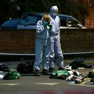 Forensics officers inspect the area outside Landor House in Camberwell, south-east London, after four people were taken to hospital with stab wounds (Jonathan Brady/PA)