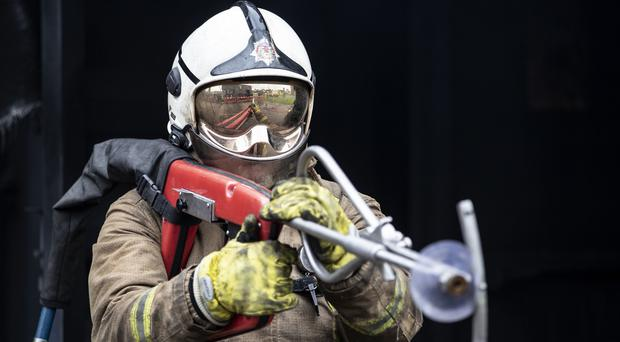 Firefighter watch manager Paul Halliday demonstrates a ultra high pressure lance (Jane Barlow/PA)