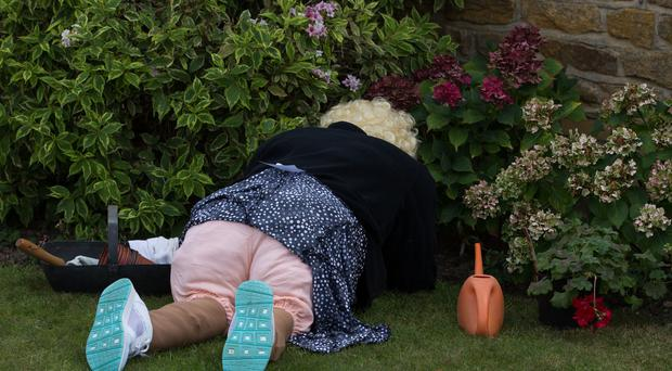 Bottoms up: Scarecrow gardener gets busy in the flower beds at the 21st annual Harpole Village Scarecrow Festival 2018 (Aaron Chown/PA)