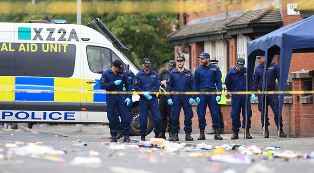 Police from the tactical aid unit carry out a fingertip search following the shooting (Peter Byrne/PA)