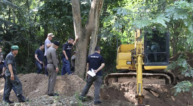 Thai officers stand by the area where the bodies of a murdered Briton and his Thai wife were found (Daily News via AP)