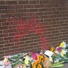 Flowers left at the scene where a homeless man was sprayed with paint