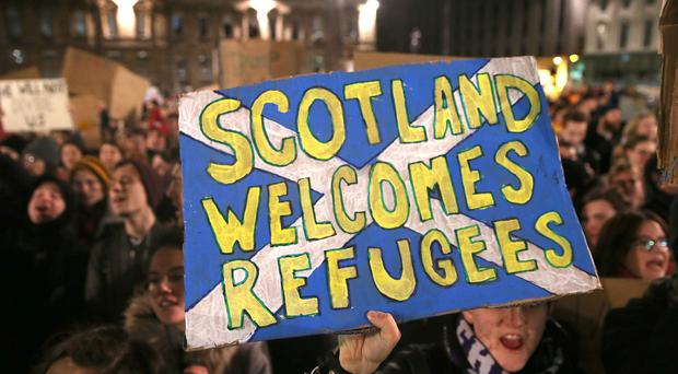 A pro-refugees banner (Andrew Milligan/PA)