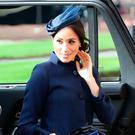 Meghan in a wide-fitting Givenchy coat at Princess Eugenie's wedding