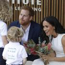 The Duke and Duchess of Sussex receive bouquets from Finley Blue and Dasha Gallagher at Taronga Zoo (PA)