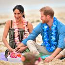 The Duke and Duchess of Sussex sitting with surfing community group OneWave