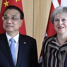 Prime Minister Theresa May greets China's Premier Li Keqiang during a meeting on the sidelines of an EU-ASEM summit in Brussels (Piroschka van de Wouw/AP)