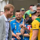The Duke of Sussex reacts as Australian Invictus Games athlete Benjamin Yeomans puts a pair of swimming trunks on his head (Dominic Lipinski/PA)