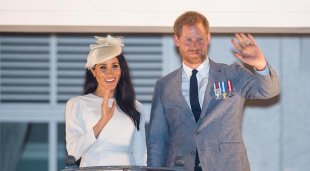 The Duke and Duchess of Sussex wave from the balcony of the Grand Pacific Hotel, in Suva, Fiji (AP)