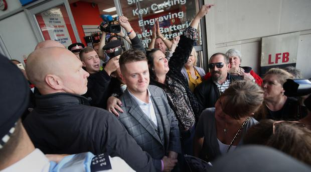 Tommy Robinson surrounded by supporters (PA)