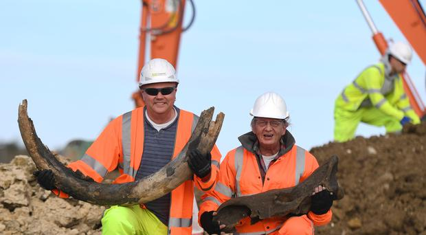 Excavator machine operator Darren Hickman (left) and MOLA Headland archaeologist Bill Boismier hold the tusk of a woolly mammoth and the skull of a rhino, believed to be around 130,000 years old, which were found during work on the A14 improvement scheme between Cambridge and Huntingdon. (Joe Giddens/ PA)