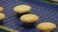 Mince pies travel along a conveyor belt ready to be packed into boxes (PA)