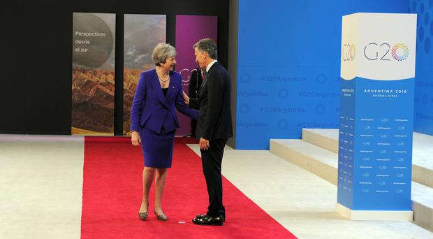 Handout photo of Theresa May being greeted at the G20 summit in Buenos Aires by Argentine president Mauricio Macri (G20 Argentina/PA Images)