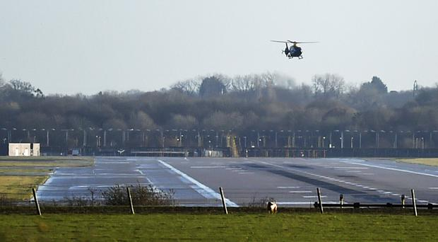 A police helicopter flies over the runway at Gatwick airport (Pete Summers/PA)