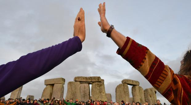 People join hands as they gather at Stonehenge in Wiltshire to mark the Winter Solstice (Ben Birchall/PA)