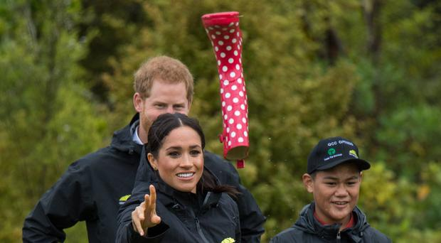 The Duchess of Sussex takes part in a welly wanging contest (Dominic Lipinski/PA)
