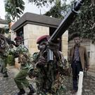 Kenyan security forces aim their weapons up at buildings as they run through a hotel complex in Nairobi (Ben Curtis/AP)