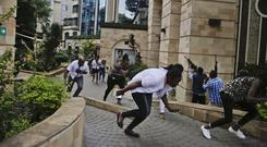 Civilians flee as security forces aim their weapons at the buildings of a hotel complex in Nairobi, Kenya (Khalil Senosi/AP)