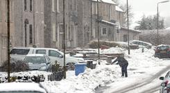 A person shovels snow from the pavement during snowy conditions last winter (Andrew Milligan/PA)
