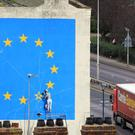 A lorry heading for the Port of Dover in Kent passes the Brexit-inspired mural by artist Banksy (Gareth Fuller/PA)
