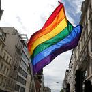 A rainbow flag is held aloft as the Pride in London parade makes its way through the streets of central, London.