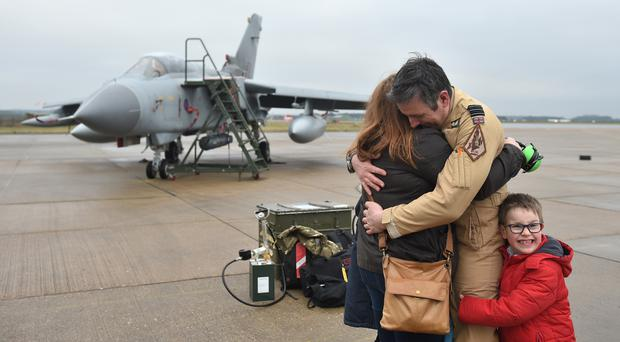Officer Commanding IX Squadron Wing Commander James Heeps with his wife and son after piloting the last RAF Tornado GR4 back to their home base at RAF Marham in Norfolk (Joe Giddens/PA)