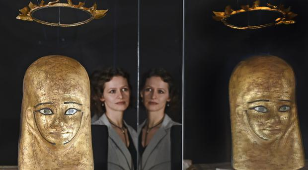 Assistant conservator Lydia Messerschmidt views the mummy mask and wreath of Montsuef at the National Museum of Scotland (Neil Hanna/NMS/PA)
