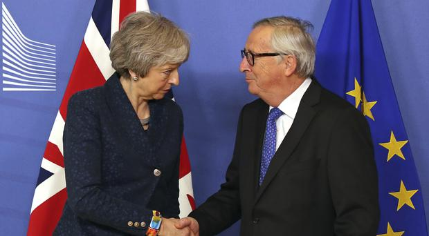 European Commission President Jean-Claude Juncker shakes hands with Prime Minister Theresa May (AP Photo/Francisco Seco)
