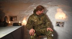 Harry looking at one of his wedding photos on the wall of a Quincey Shelter in Norway (Victoria Jones/PA)